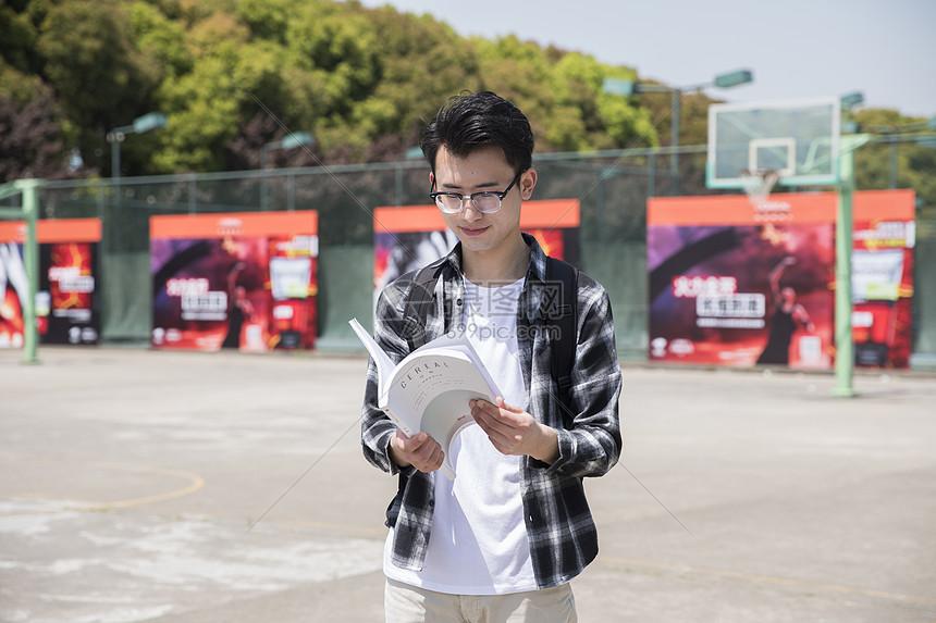 先生在篮球场看书阅读图片