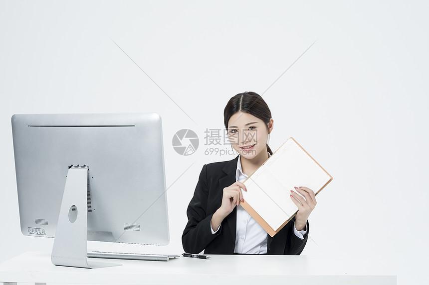 拿着笔记本的职业女性图片