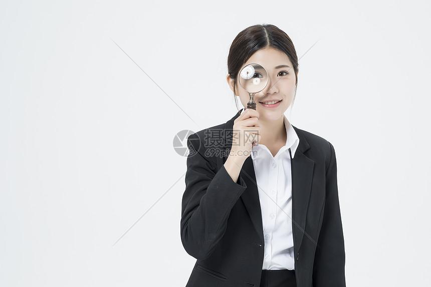 拿着放大镜的职业女性图片