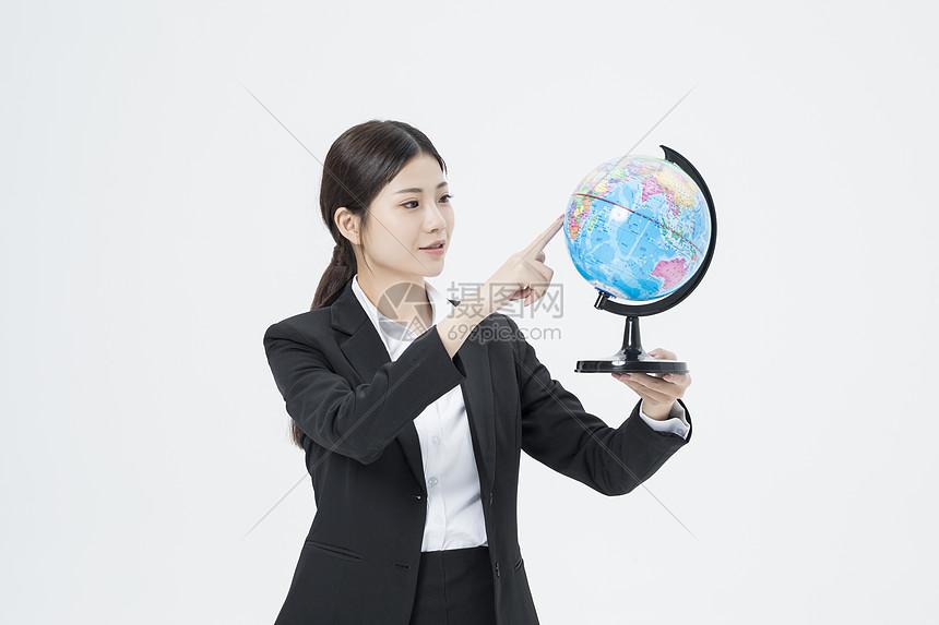 拿着地球仪的职业女性图片
