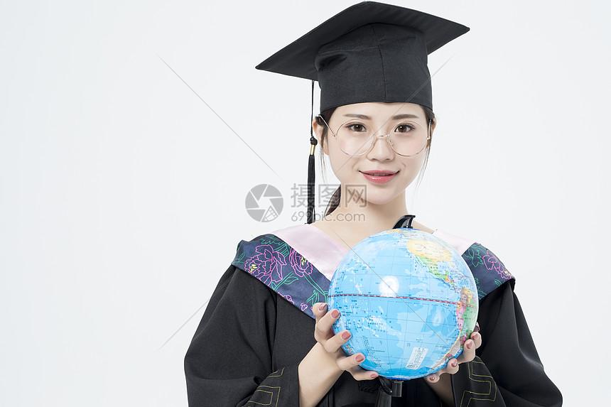 拿着地球仪的毕业女大学生图片