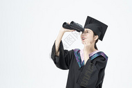 拿着望远镜的毕业女大学生图片