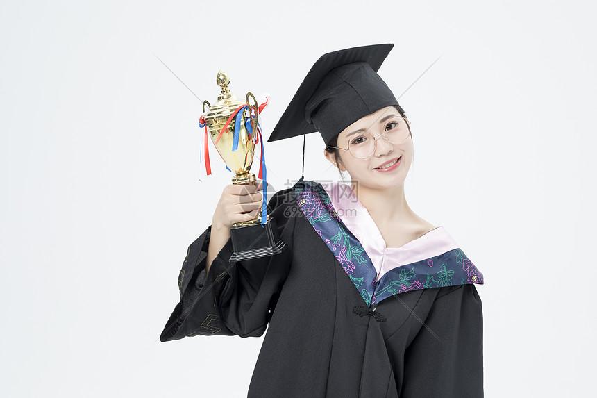 拿着奖杯的毕业女大学生图片