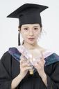 拿着灯泡的毕业女大学生图片