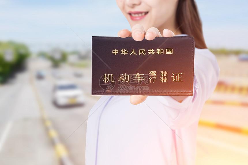 拿着驾驶证的女性图片