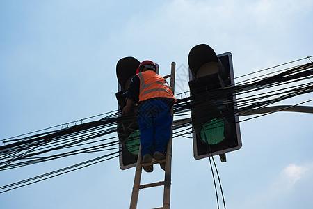 蓝天下维修线路的工人图片