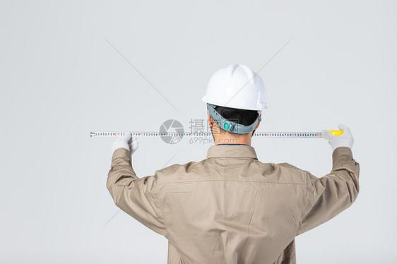 工人用卷尺做测量工作图片