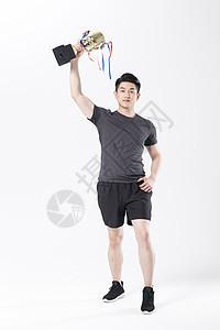拿着奖杯的运动男性图片