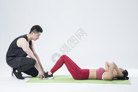 帮助女生仰卧起坐的男性图片