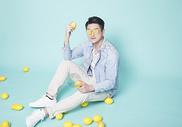 坐在地上拿着柠檬的青年男性图片