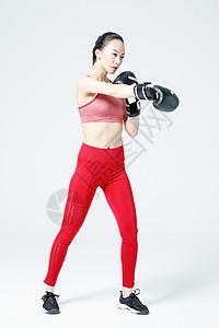 健身女性戴拳击手套展示动作图片