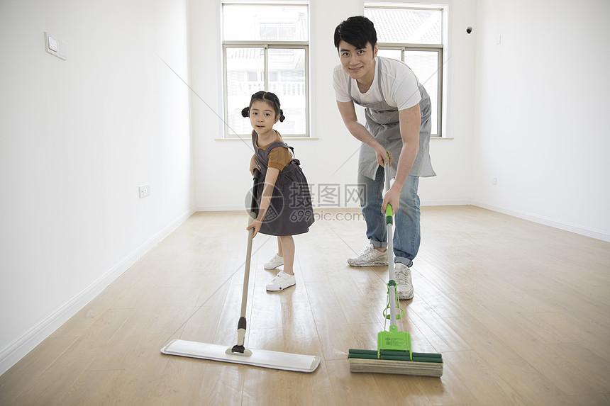 爸爸和女儿在新家拖地图片
