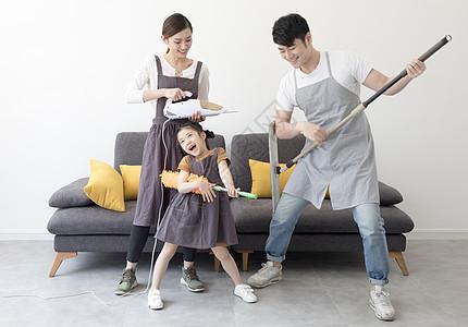 拿着清洁工具玩闹的一家人图片