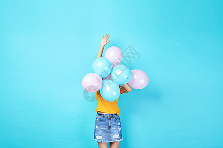 青年活力女性手持彩色气球图片
