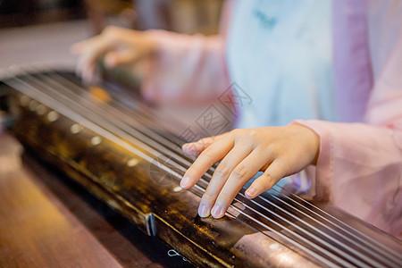 穿中国传统服饰的女性弹奏古琴图片