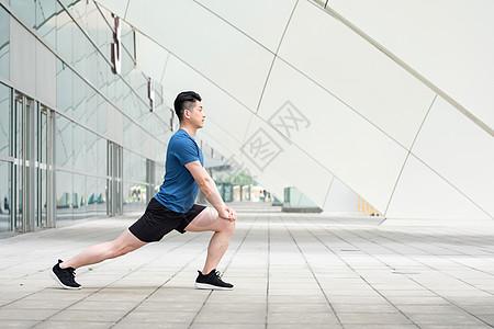 年轻男性户外运动热身压腿拉伸动作图片