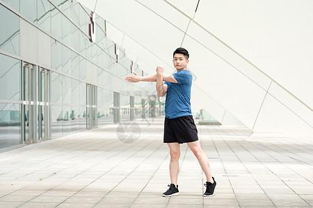 年轻男性户外运动热身拉伸动作图片