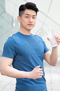 运动健身后站着喝水的年轻男性图片