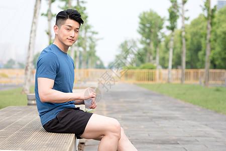 运动后坐着休息喝水放松的年轻男性图片