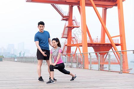 教练指导年轻女子热身运动户外锻炼图片