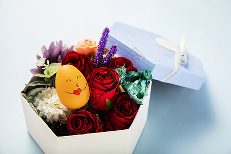 蓝色背景上装满鲜花的礼物盒图片