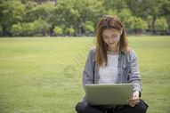 女学生在大学草坪上学习图片