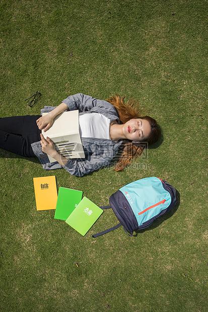 女学生躺在大学草坪上看书图片