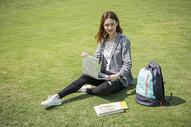 女学生在大学草坪上看电脑图片