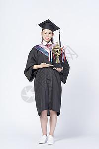 拿着奖杯的毕业女学生图片