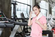年轻美女健身房休息擦汗图片