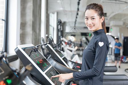 年轻女性健身房使用跑步机跑步图片