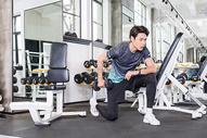 男子健身房使用哑铃运动健身训练图片