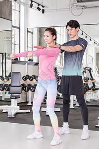 健身教练指导学员运动健身举哑铃图片