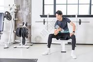 年轻男性健身房举哑铃力量训练图片