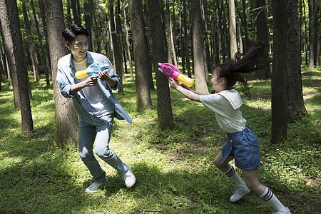 爸爸与孩子在树林中玩水枪图片