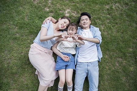 户外一家人躺在草坪上图片
