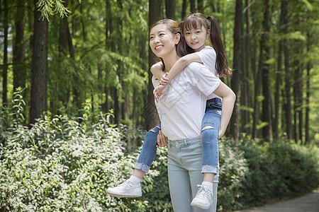 妈妈背着女儿在公园走路图片