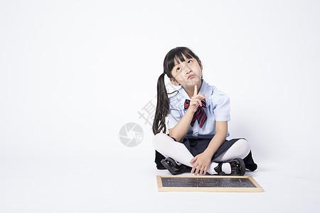 在动脑经的拿着黑板的小女孩图片