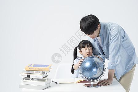 一起观察地球仪的老师和学生图片
