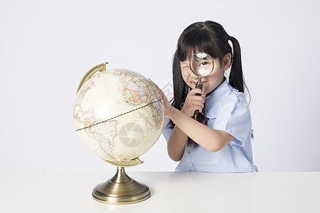 观察地球仪的小女孩图片