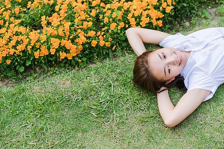 校园写真女生躺在草地上图片