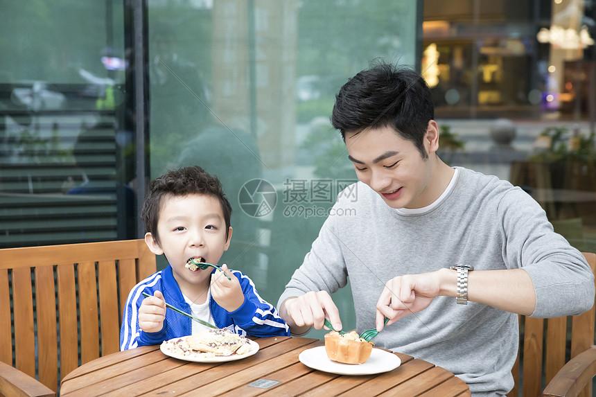 带着孩子吃东西的父亲图片