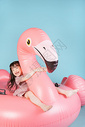 小女孩儿童节在充气火烈鸟上玩耍图片