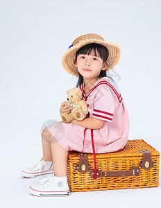 坐在旅行箱上的小女孩图片