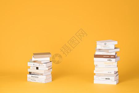 简洁黄色背景上的书堆图片