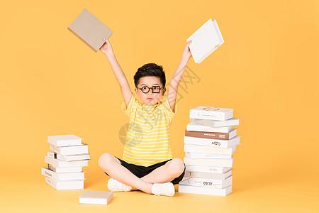 拿着书本坐在书旁的快乐男孩