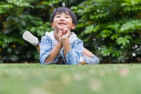 可爱儿童开心趴在草地上图片