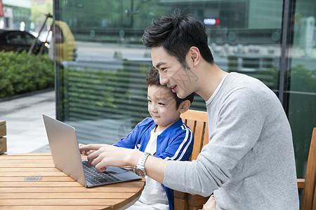 咖啡馆看电脑的父子图片