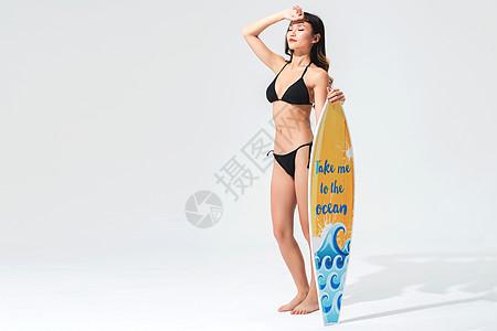 黑色比基尼泳装美女手持冲浪板图片