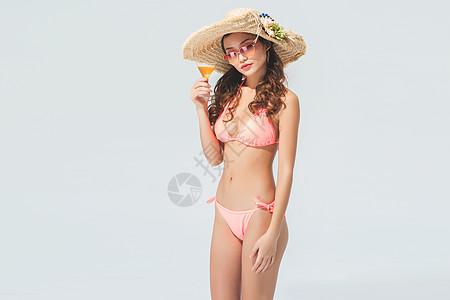 穿粉色比基尼的美女头戴遮阳帽喝饮料图片